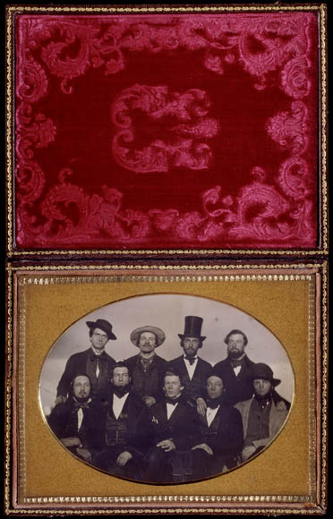 A velvet-lined case with a daguerreotype portrait of nine men: five seated in front, four standing.