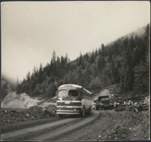 A black-and-white photograph of a public bus travelling on a gravel road and passing a construction crew working in the background. The area is mountainous.