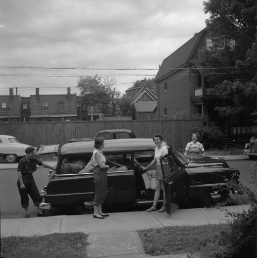 A black-and-white photograph of four women posing around a station wagon packed for a road trip.