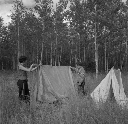 A black-and-white photograph of two women putting up two tents in a meadow with long grass surrounded by trees.