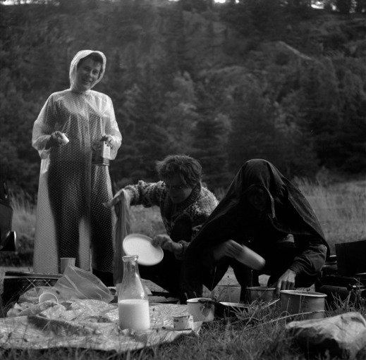 A black-and-white photograph of three women in a wooded area preparing dinner in the rain.
