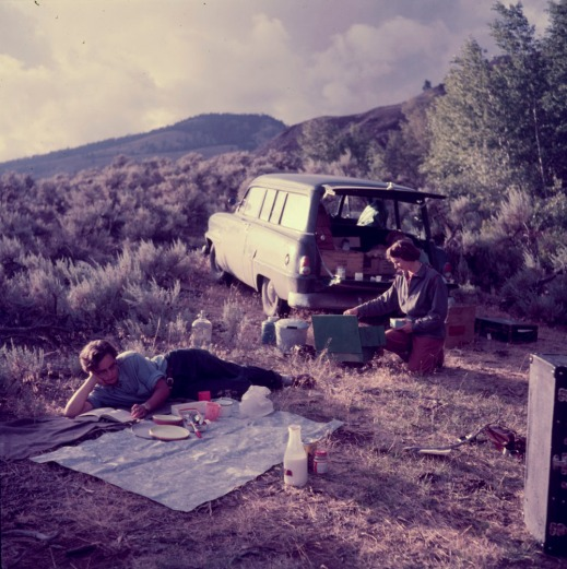 A colour photograph of two women in a grassy area with mountains in the distance—one is reading reclined on a picnic blanket and the other is kneeling at a camp stove located behind a station wagon.