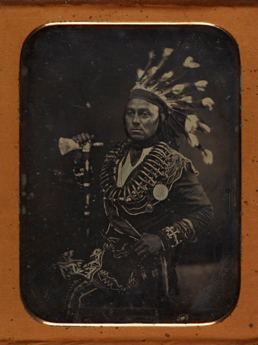 Daguerreotype portrait of Maungwudaus wearing ceremonial dress including a feathered headdress and two medals.