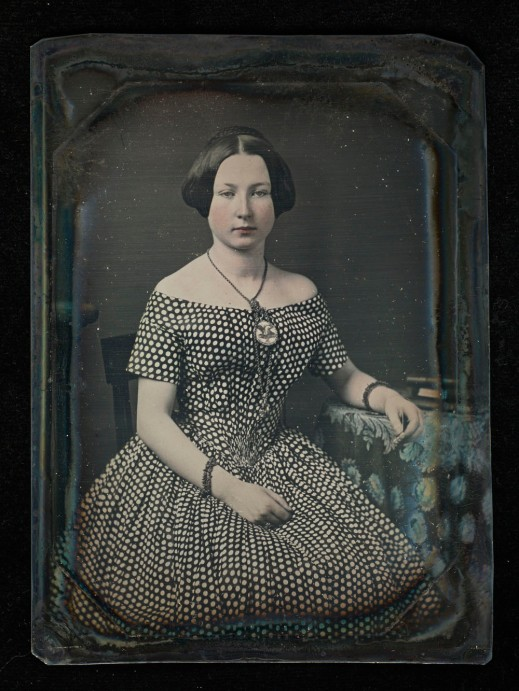 A hand-tinted daguerreotype portrait of a seated woman in a polka-dot dress.