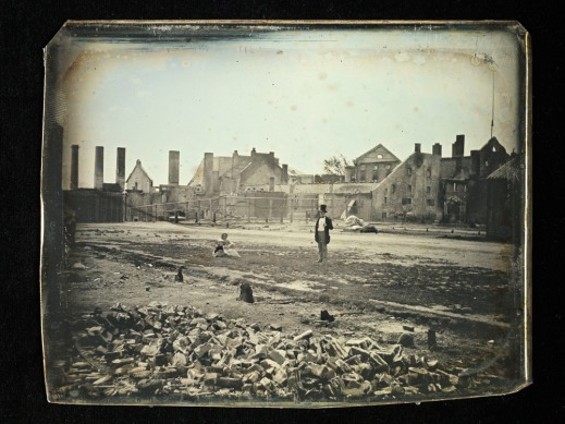 A daguerreotype photograph of a man (standing) and a woman sitting on the ground, among the destroyed remains of the brewery.