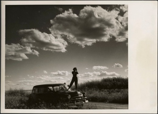 A black-and-white photograph of a woman in silhouette taking a photograph while standing on the hood of a station wagon parked on the side of the road in the prairies.