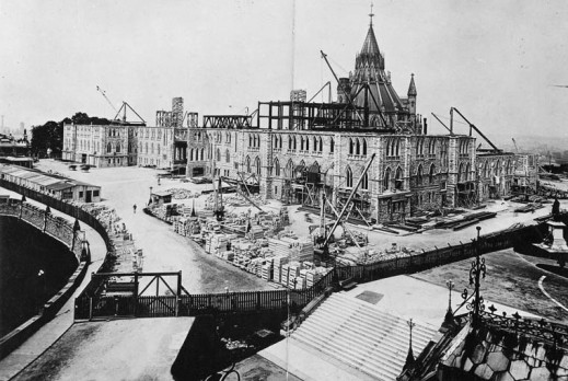 A black-and-white photograph showing the first three stories of a building with the rotunda of the Library of Parliament in the background. Cranes and construction materials surround the area.