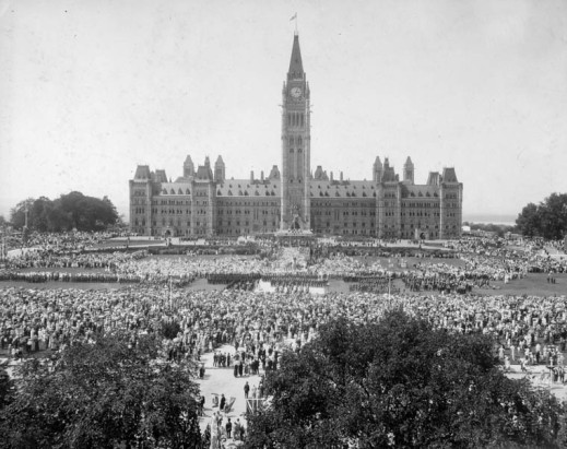 A black-and-white photograph showing the main Parliament building from the front with crowds of people filling Parliament Hill.