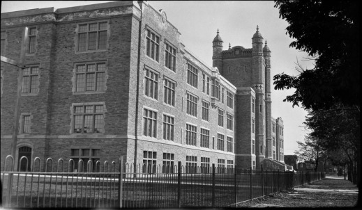 A black-and-white photograph showing a large building taken from the side.
