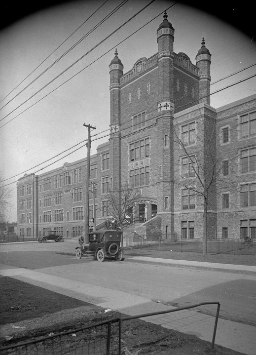A black-and-white photograph showing the front entrance of a building. There are two cars parked in front of it and a few people standing at the entrance.