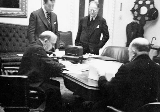 A black-and-white, slightly blurred photograph of four men in suits in an office around a table covered with documents. Two are seated and looking at papers, while the other two stand, overlooking the proceedings.