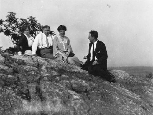 A black-and-white photograph of a group of people sitting on a high rocky ledge with blurry trees in the distant background. Everyone is looking towards the photographer except for one man who is looking at the others.