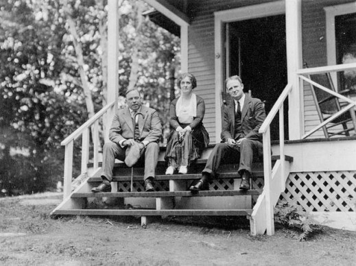 A black-and-white photograph of three people sitting on the front steps of a cottage looking towards the photographer.