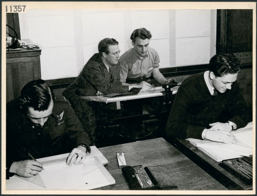 A black-and-white photograph showing a teacher working with a student at a technical school along with other students in the classroom.