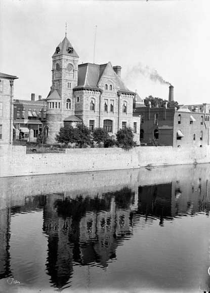 A black-and-white photograph of a castle-like building overlooking a waterway, very similar to a moat.