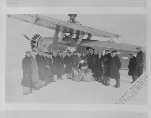 A black-and-white photograph depicting a group of men in winter coats and hats standing in front of a single-engine aircraft. The men are arranged in a semi-circle facing the camera with sacks of airmail laying on the ground.