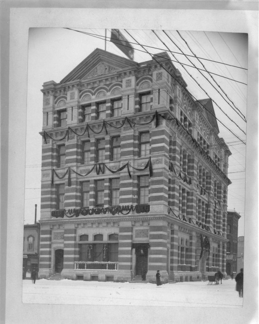 A black-and-white photograph of a building decorated with Christmas decorations and located on a snowy street. The building has bands of alternating stones and brick and is very ornate.
