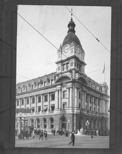 A black-and-white photograph of a very ornate building with a large clock tower in one corner. People and cars can be seen in the foreground.