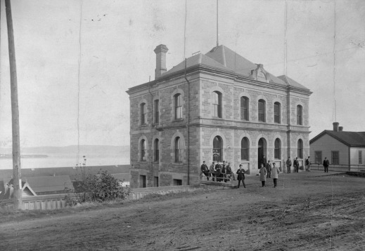 A black-and-white photograph of a small two-storey building with people standing in front of it.