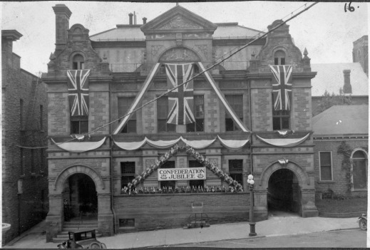 "A black-and-white photograph of a building decorated with Union Jacks and a sign that reads ""Confederation Jubilee."""