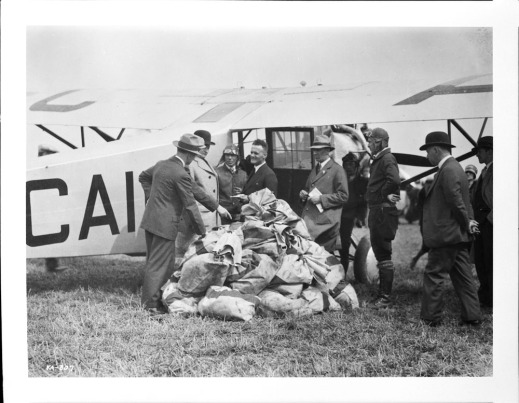A black-and-white photograph of a group of men standing in front of a single-engine aircraft. The men are arranged in a semi-circle around many sacks of mail piled on the ground.