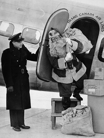 A black-and-white photograph depicts a man dressed as Santa Claus exiting the side door of an aircraft carrying a sack of airmail. He is on portable steps ready to step onto the pavement. The door is held open by a man in uniform.