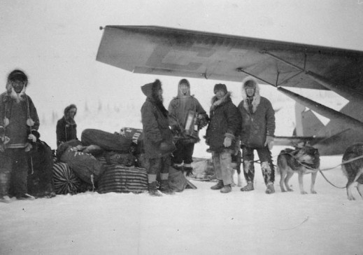 A black-and-white photograph depicting a number of men standing under the wing of an aircraft next to a dogsled loaded with sacks of airmail. Most of the men are posed, facing the camera. A number of dogs in harness are visible.