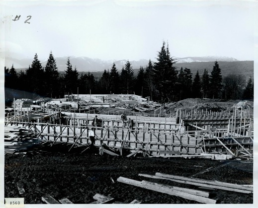 A black-and-white photograph of a construction site showing wooden forms and supports.