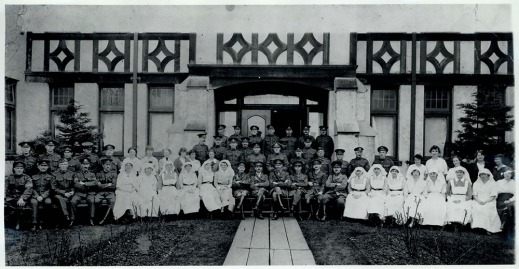 A black-and-white photograph of uniformed men and nurses seated in front of an elaborate Elizabethan entrance.