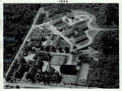 A black-and-white aerial view of a building complex.