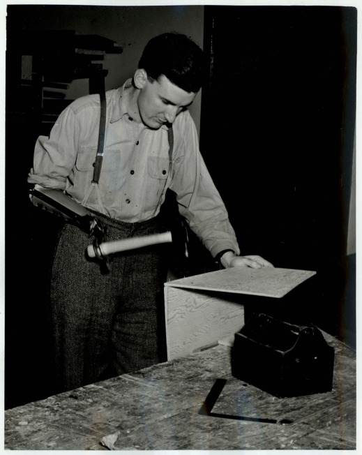 A black-and-white photograph of a man using a hammer with his prosthesis to build and assemble two pieces of wood.