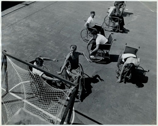 A black-and-white photograph showing seven men in wheelchairs playing a ball game around a hockey-type net.
