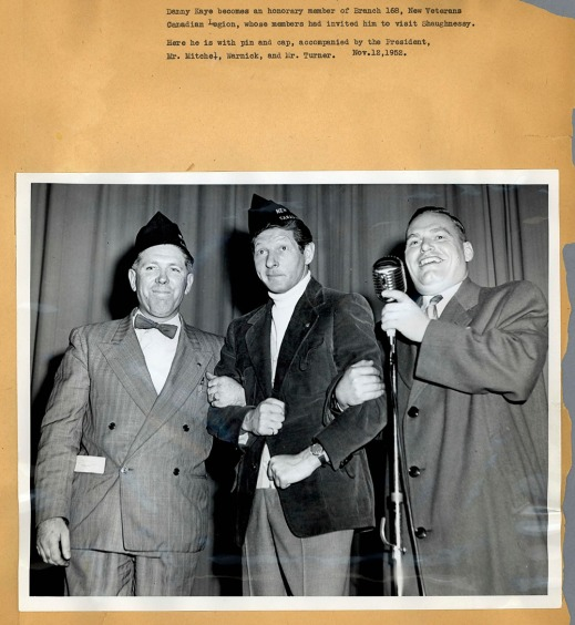 A black-and-white photograph mounted on a piece of a paper showing three men arm-in-arm around a mic. The photo is captioned.