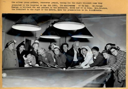 A black-and-white photograph showing a large group of women and a single man around a pool table, some of them leaning over the table and aiming at the cue ball with cues. The photo is captioned.