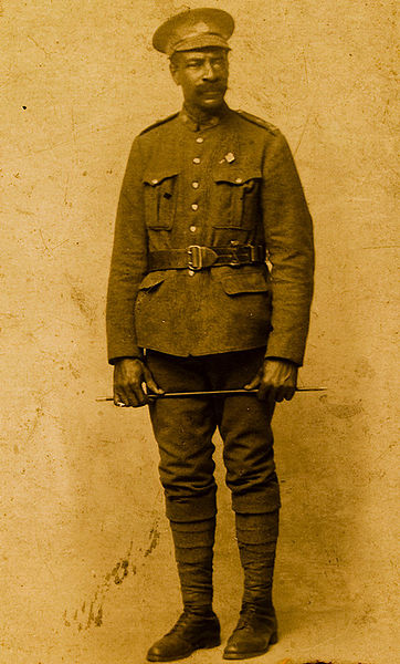 A sepia-coloured photograph of a man in uniform wearing an officer's belt and cap holding a baton in both hands across his upper thighs.