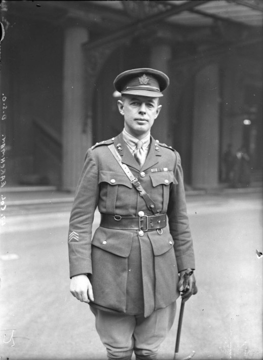 A black-and-white photograph of a man standing. He is wearing a uniform, a cap and a Sam Browne belt, and holding a baton.