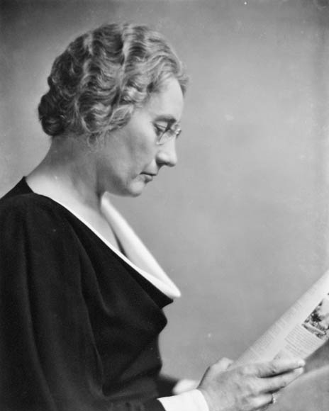 A black-and-white photograph of Agnes Macphail in profile, reading the paper.