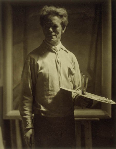 Black-and-white photograph showing a man standing up and holding a paint palette and brushes in one hand and looking a little to the side.