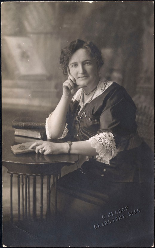 A black-and-white photograph of a seated woman, right hand propping up her head, right elbow on a table, a book in her left hand. She is looking directly at the camera.