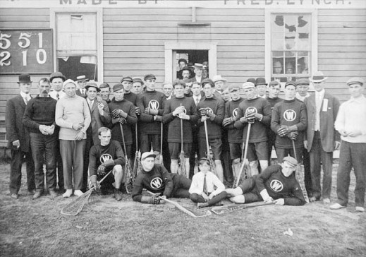 A black-and-white photograph of the New Westminster lacrosse team. The men are standing, kneeling and lying down outside in front of a small building. The players are dressed in team uniform and are holding their lacrosse sticks. Also present are men and a small boy wearing street clothes.