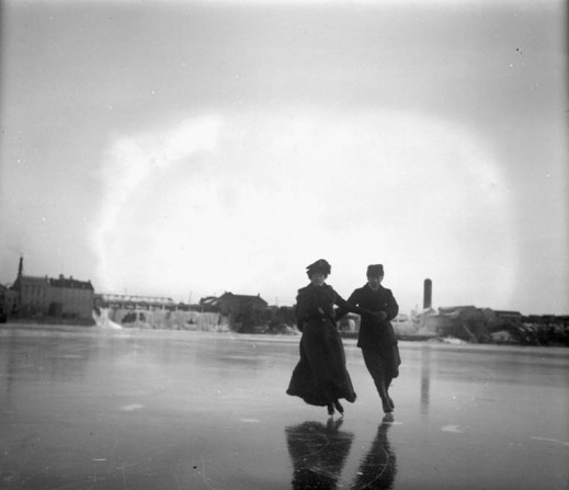 A black-and-white photograph showing a couple skating together and holding hands, dressed in winter clothing. Buildings and other structures are visible in the background.
