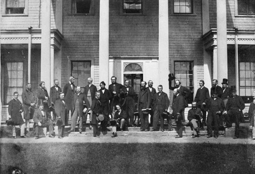 A black-and-white photograph of a group of men standing in front of a building.
