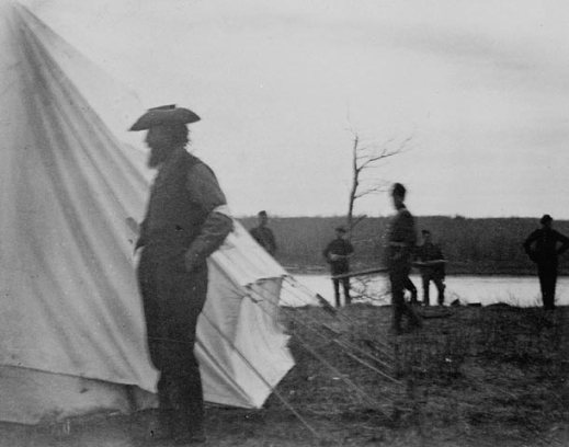A black-and-white photograph of the side view of a man standing in front of a white canvas tent with five men standing in the background.