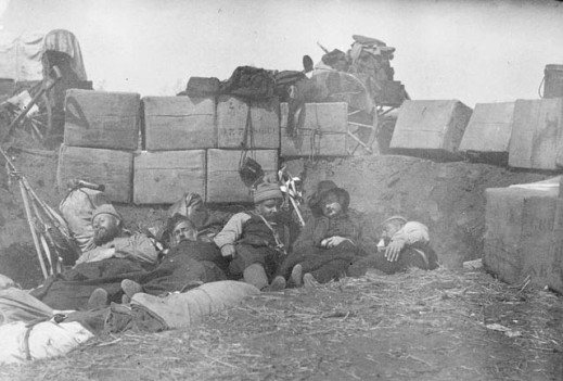 A black-and-white photograph of five men asleep on the ground behind a barricade made of earth and bundles of supplies.
