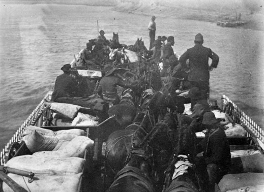 A black-and-white photograph of men, horses and supplies on a ferry crossing the South Saskatchewan River.