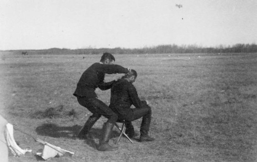 A black-and-white photograph of a soldier cutting the hair of a seated soldier in a field.