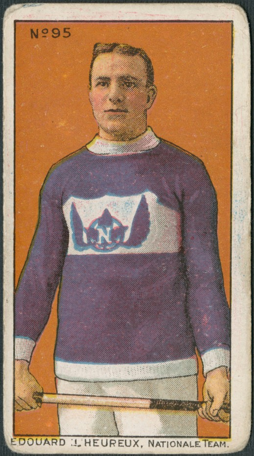 "A trading card with a colour print of a man wearing a purple sweater with white trim and holding a lacrosse stick with both hands. On the sweater is a purple maple leaf with purple wings and adorned with a white ""N."" It is captioned: ""Edouard L'Heureux, Nationale Team."""