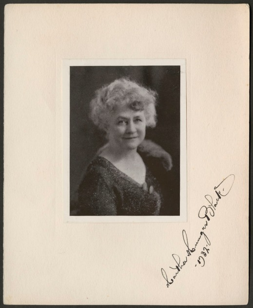 A signed and matted black-and-white photograph of a woman smiling, dated 1932.