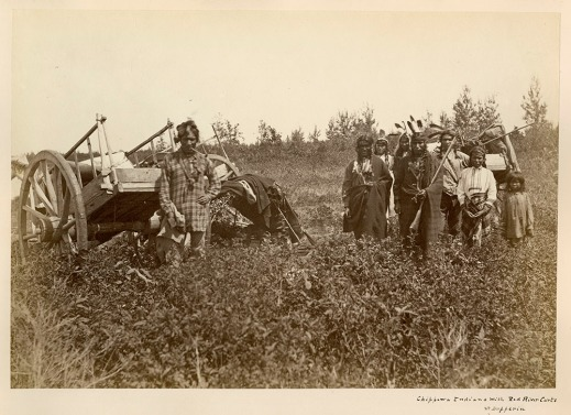 Black and white photograph of a man, on the left, wearing European clothing and standing in front of a Red River cart, and a group of First Nations men, women and children wearing First Nations-style clothing and standing in front of another Red River cart, on the right.