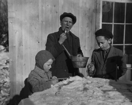 A black-and-white photograph showing three people eating maple taffy on snow.